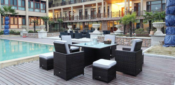 Rotting spisegruppe i brunmix farge med stort bord med glassplate. Det er fire stoler med høy rygg og paller til. Står ved et hotell med svømmebasseng og palmer   SparMax
