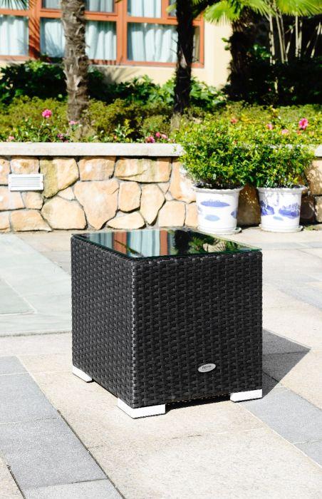 Lite rotting sidebord i sort farge med glassplate  som står ute på uteplassen med blomster. SparMax