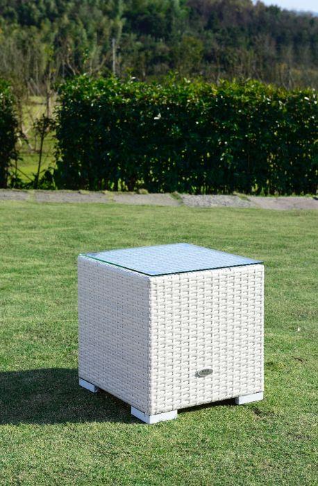 Hvitt lite sidebord i rotting med glassplate som står i hagen på uteområdet. Det er en hekk i bakgrunnen - SparMax.