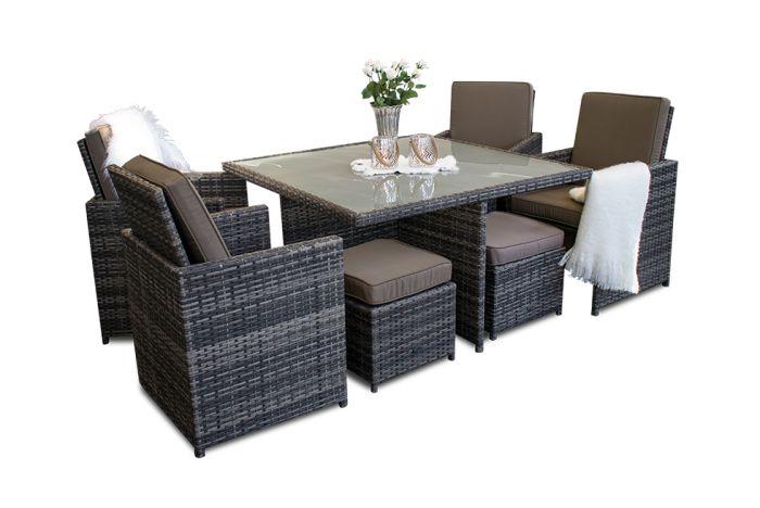 Fin utendørs spisegruppe i rotting med fire fotskamler. Det er stoler med høy rygg og puter i både stoler og puffer. Det er et teppe i den ene stolen. på bordet med glassplate står det en vase med blomster. Hagemøblene er i gråmix farge | SparMax