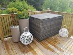Stor putekasse i kunstrotting som står på en terrasse sammen med krukker og lysholdere-  SparMax