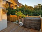 Nydelig putekasse i grå rotting på en veranda. Det er skog og planter sammen med lyslamper- SparMax