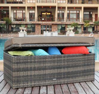 Fin vedlikeholdsfri og vanntett putekasse og sittebenk med pute på lokket, som er forsterket. Det er mange fargerike puter i putekassen som er åpnet på gløtt. Putekassen står på en veranda ved et svømmebasseng- SparMax